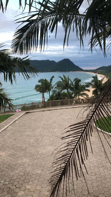 Vista do Morro das Pedras, em Florianópolis, mostrando uma bela praia e morros ao fundo, num dia levemente nublado