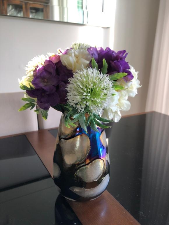 Vaso de flores artificiais, mostrando flores brancas e roxas